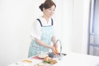 岡江さんがキッチンでにんじんを洗っている画像