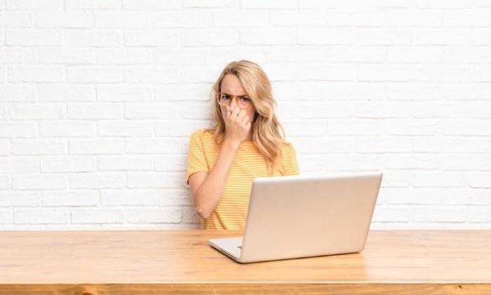 パソコンの前で鼻をつまむ女性の画像