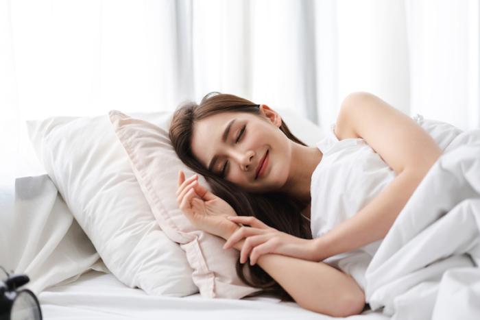 ベッドで気持ちよさそうになている女性