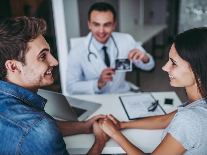 医師から妊娠の結果を聞くカップル