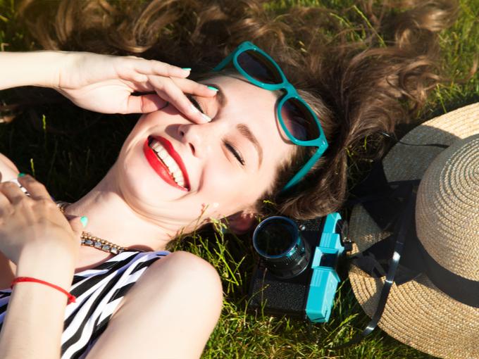 芝生に寝転がり、笑顔の女性