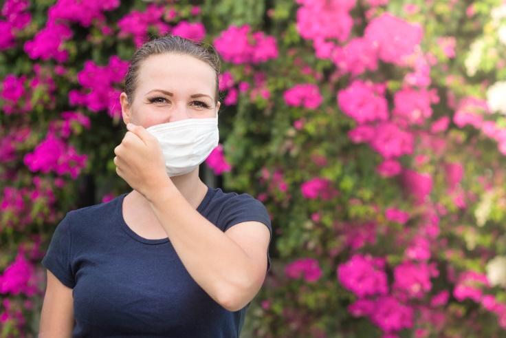 マスクを外しかけている女性の画像