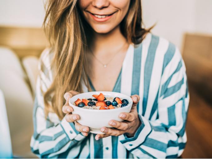 果物とオートミールのボウルを持つ女性