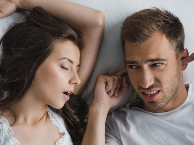 いびきをかく女性の横で耳をふさぐ男性