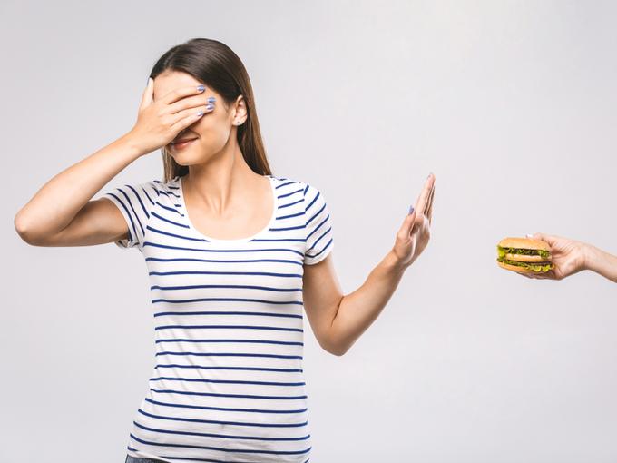 差し出されたハンバーガーを遠慮する女性