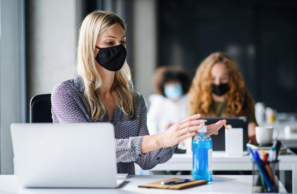 手の消毒をしてマスクをつけている職場の女性