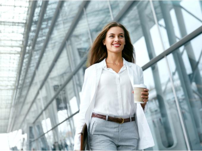 コーヒー片手に仕事に向かうスタイリッシュな女性