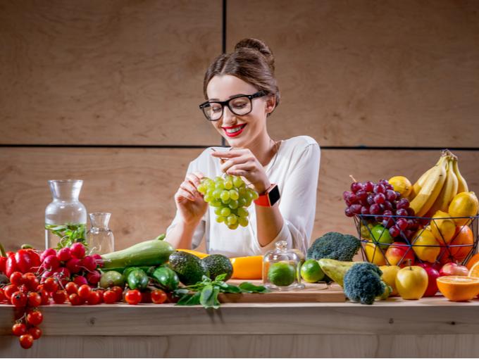 果物や野菜に囲まれた女性
