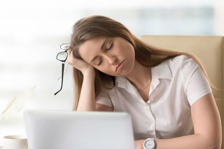 机に肩ひじをつく女性の画像