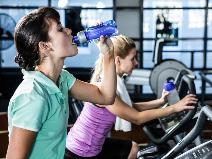 スポーツジムで水分補給をする女性