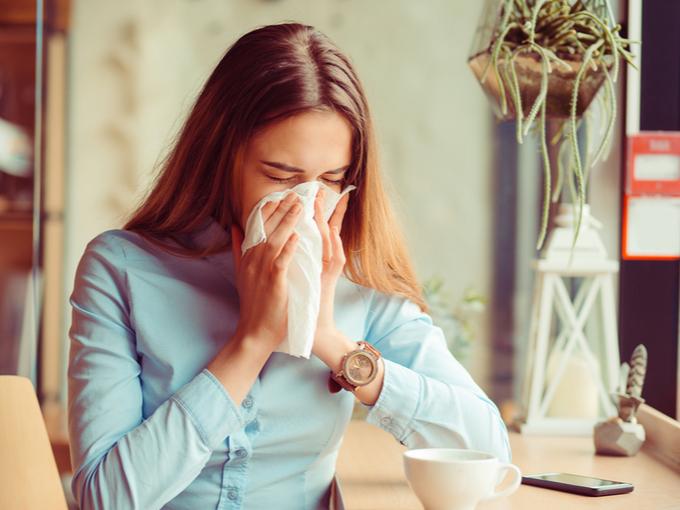 アレルギーで鼻をかむ女性