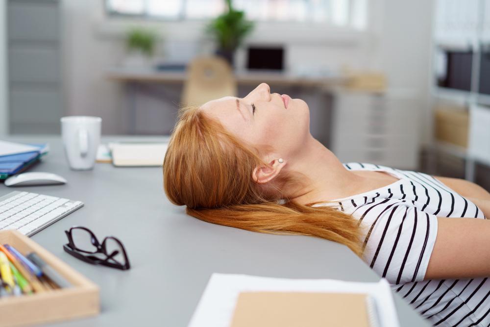 仕事中にデスクでお昼寝する女性