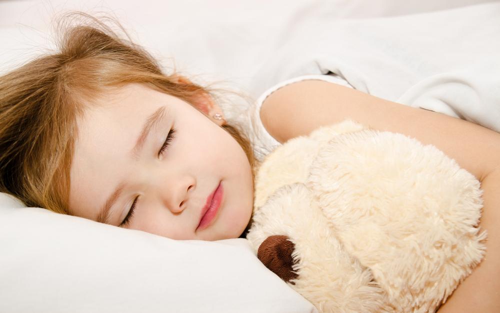ぬいくるみを抱いて寝る女の子
