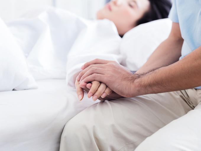 病床の患者の手を握る男性