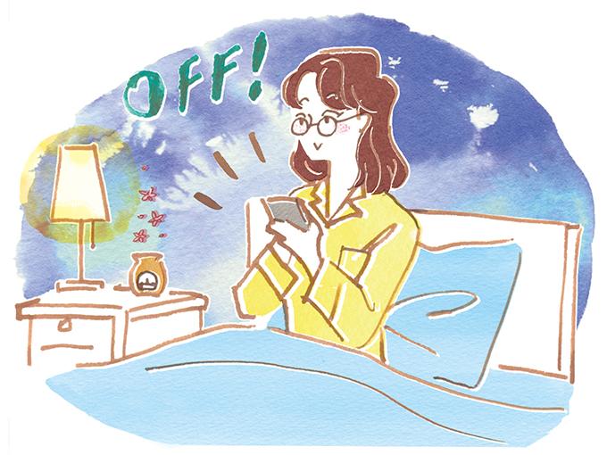 ベッドで携帯電話の電源をオフにする女性
