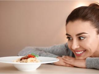 お皿に盛られたパスタを見る女性