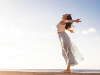 浜辺で両手を広げ、解放感に満ちあふれる女性