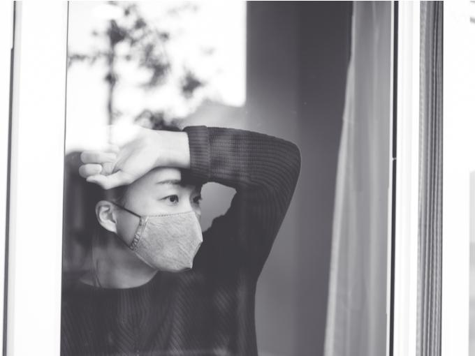 窓の外を見つめるマスク姿の女性