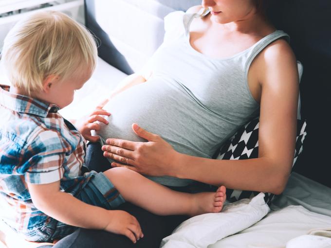 我が子と一緒に自分のお腹に触れる妊婦