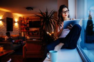 夜の窓のそばでデジタル機器を操作している女性