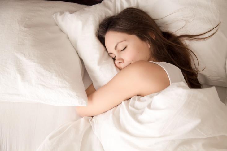 枕を抱えて眠る女性の画像