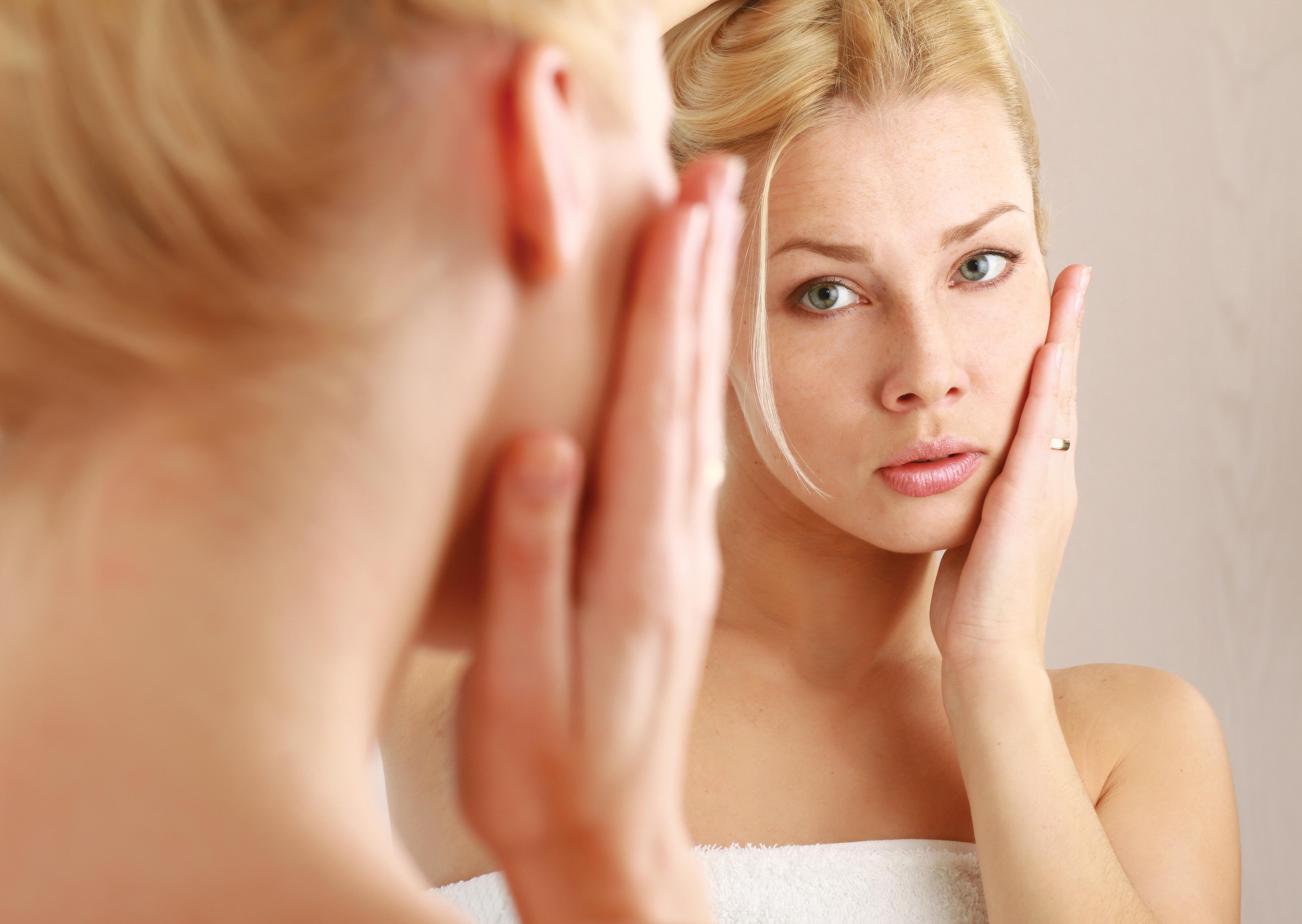 鏡を見ながら頬にてを当てている女性