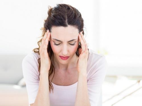 頭痛でツラそうな女性