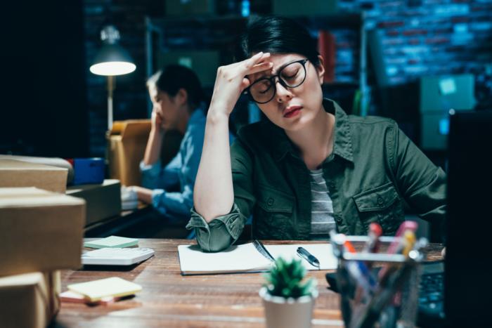 夜の仕事で疲れて頭を抱えている女性