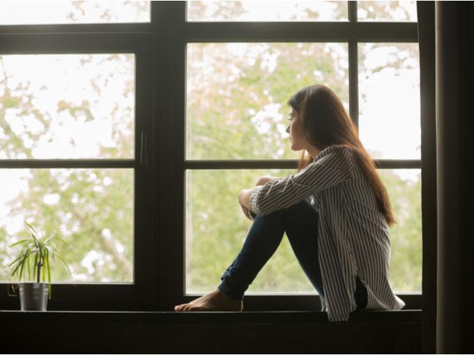 窓辺で物思いにふける女性