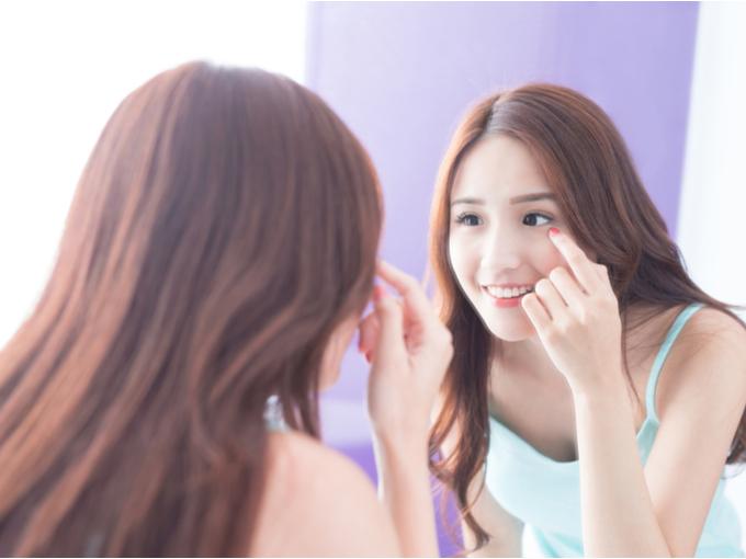 目を鏡でチェックする女性