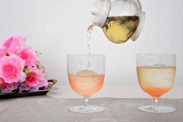 グラスにピンク色のお茶を注いでいる