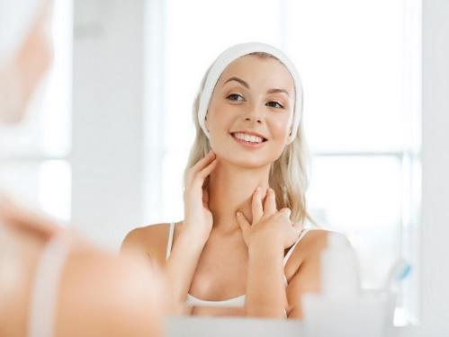 首に手をあてて鏡を見ている女性