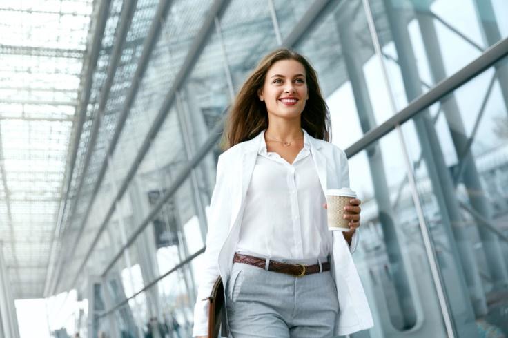 紙コップをもって歩く女性の画像