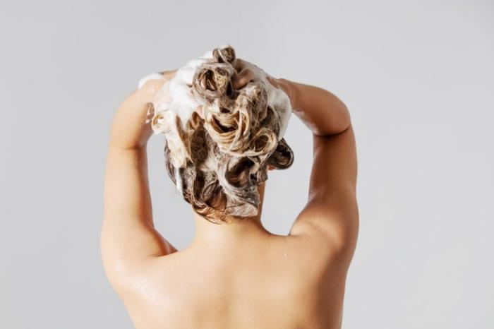シャンプーをする女性の後ろ姿画像