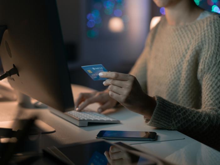 クレジットカードを片手にパソコンを操作している女性の手もと