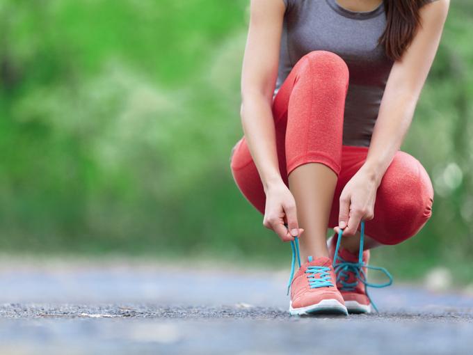 ランニング前に靴紐を結び直す女性