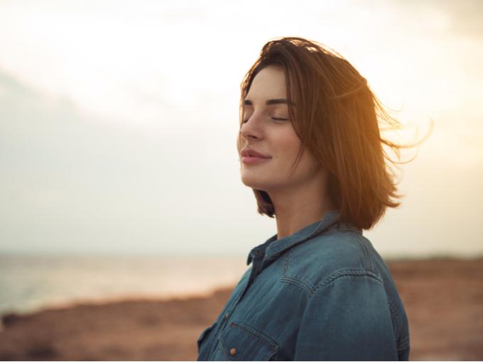 浜辺に立ち、リラックスして充実した表情の女性