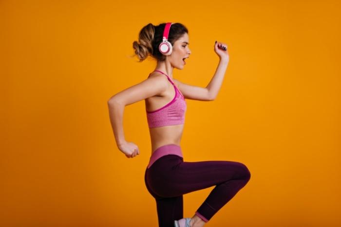 ヘッドフォンをつけて走るポーズをする女性の画像