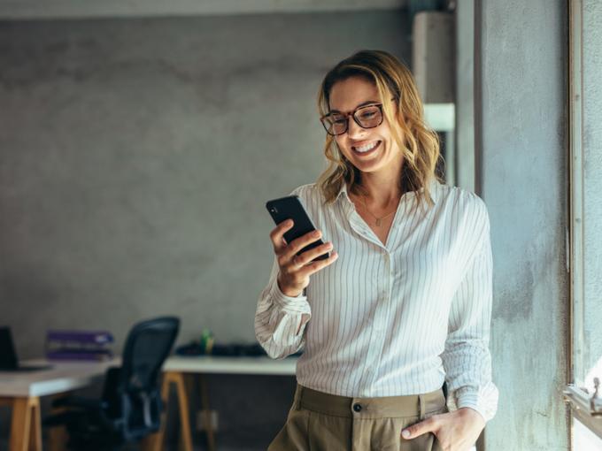 携帯電話のオンライン通話で笑顔で話す女性