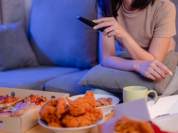 夜、テーブルにピザやフライドチキンを並べ、テレビリモンコンを手にする女性