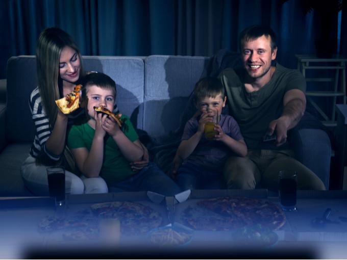 夜テレビを見ながらピザを食べる親子