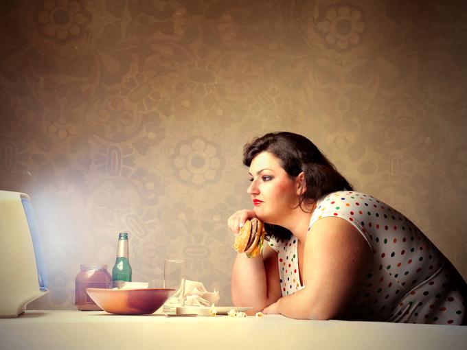 テレビを見ながらハンバーガーを食べる女性