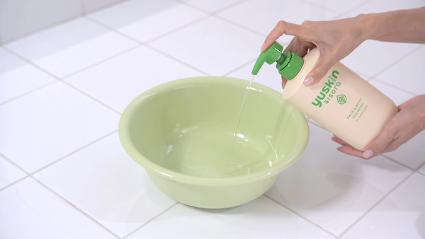 両手ひとすくい程度のぬるま湯を洗面器に入れ、洗浄剤を2〜3プッシュ入れる様子