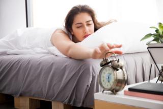 眠そうに目覚まし時計を止めようとしている女性