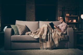 夜に女性が本を読んでいる画像