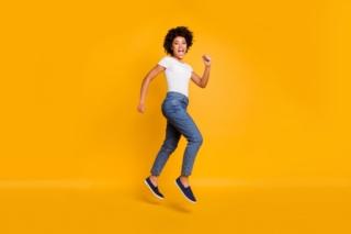 オレンジの背景で跳んでいる女性の画像