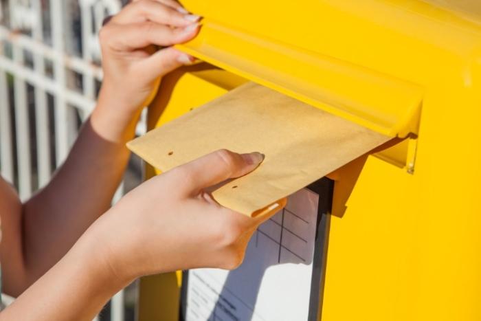黄色いポストに手紙を入れる画像