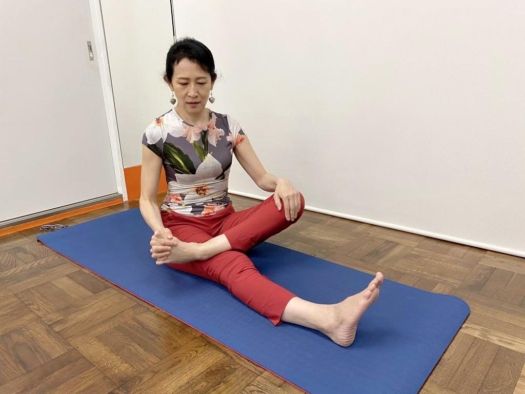 左足のつま先と左手で握手している画像
