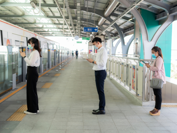 ソーシャルディスタンスをとって電車を待つ人
