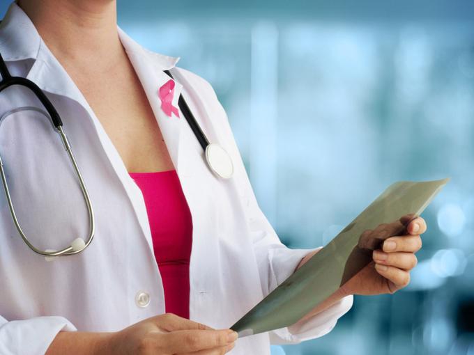 ピンクリボンをつけた女性ドクター